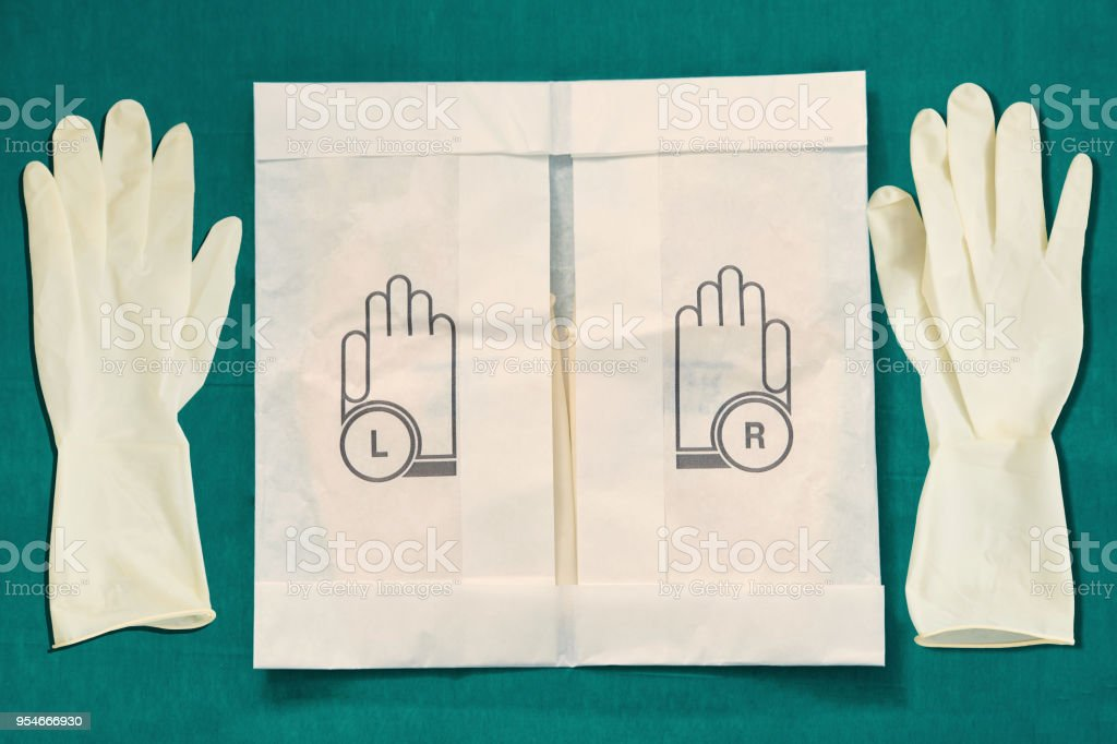 Disposible sterile rubber,one time used Gloves with paper package on green signature of surgery dress stock photo