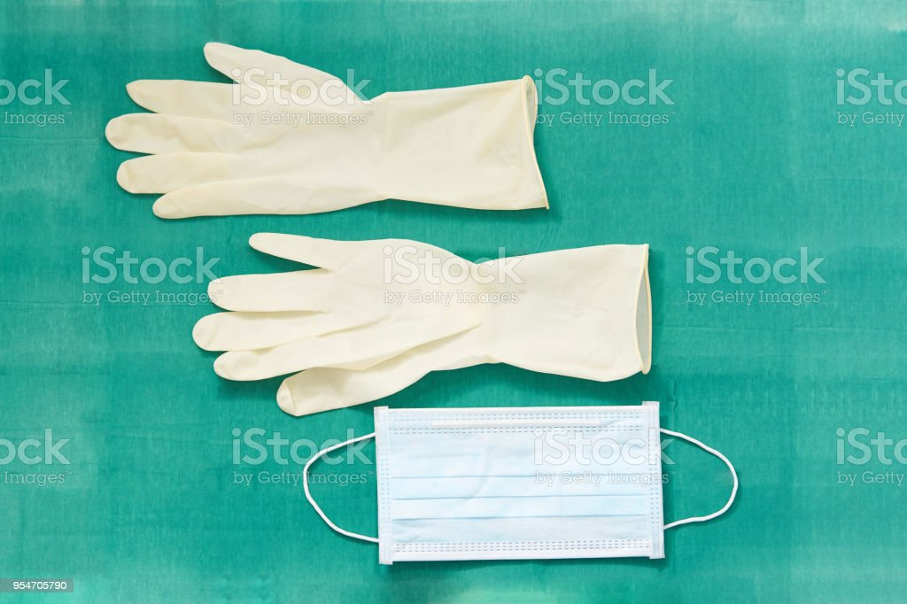 Disposible sterile rubber,one time used Gloves with surgeon mask on green signature of surgery dress stock photo