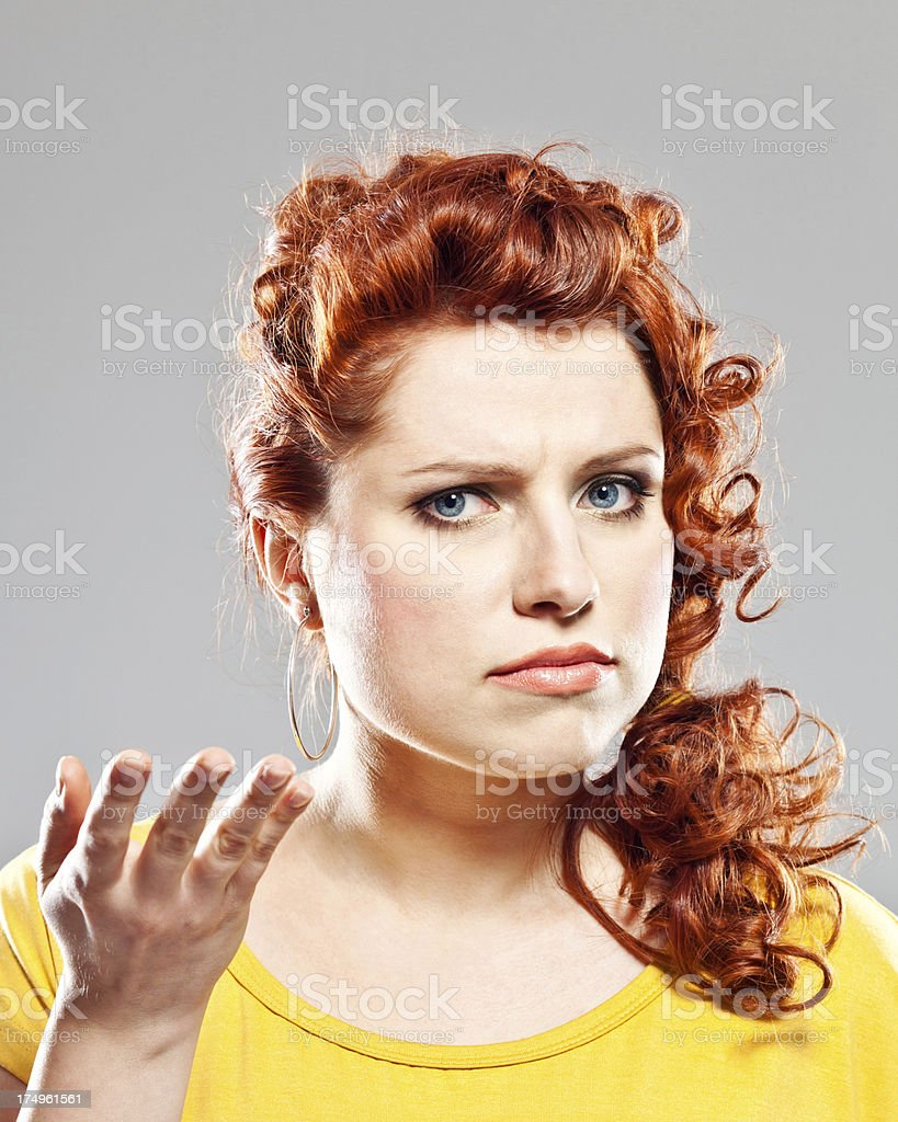 Dissatisfaction Portrait of displeased young woman looking at camera. Studio shot. 20-24 Years Stock Photo
