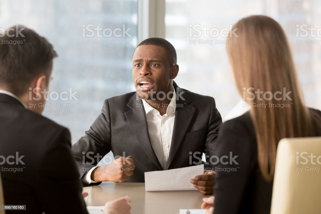 Dissatisfied african-american boss clenching fist, scolding employees for bad work stock photo