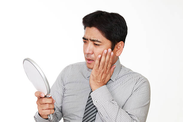 Dissatisfied Asian man Asian man looking at his face in mirror hair stubble stock pictures, royalty-free photos & images