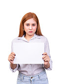 dissatisfied Asian woman holding blank white paper banner for protested with frown face. studio portrait shot isolated on white background with clipping path