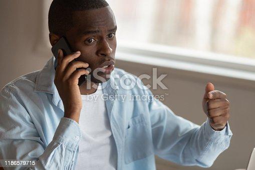 824614192 istock photo Dissatisfied biracial man having unpleasant cellphone conversation 1186579715