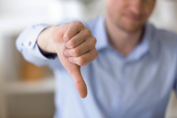 Dissatisfied business man showing thumbs down at workplace Close up of unrecognizable businessman with dissatisfied face showing negative sign, dislike with thumbs down, rejection concept at workplace, sign no, not approved, unhappy customer rejection stock pictures, royalty-free photos & images