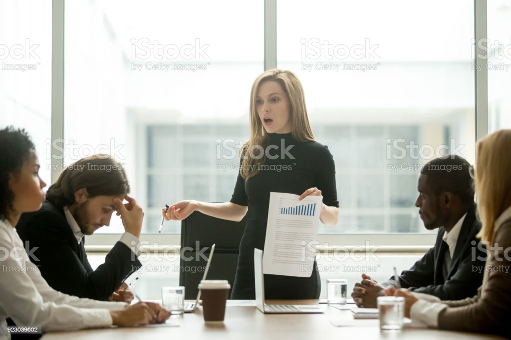 Dissatisfied female executive scolding employees for bad work at meeting stock photo