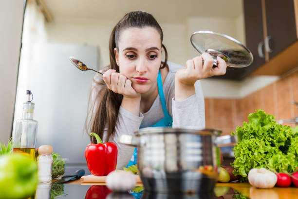 dissatisfied housewife trying to prepare healthy meal. cooking learning problems. - fail cooking imagens e fotografias de stock