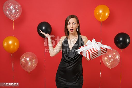 istock Dissatisfied shocked girl in black dress spreading hands, hold red box with gift, present on bright red background air balloons. Valentine's Day, Happy New Year, birthday mockup holiday party concept. 1132755327