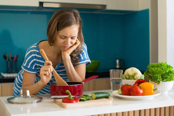 missnöjd kvinna matlagning och tittar in pan - food woman to smell bildbanksfoton och bilder