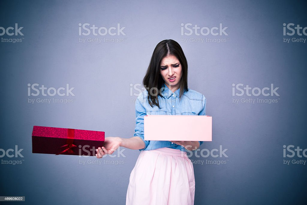 Dissatisfied woman opening gift stock photo