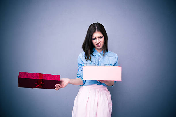 dissatisfied woman opening gift - disappointment stock pictures, royalty-free photos & images
