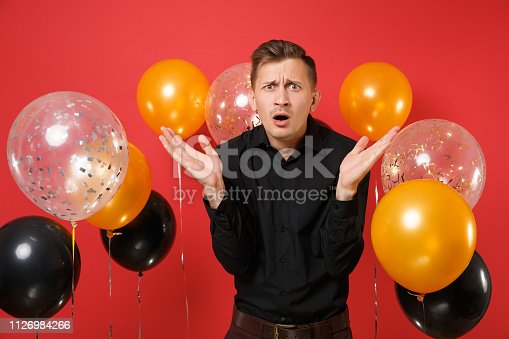 istock Dissatisfied young man in black classic shirt spreading hands on bright red background air balloons. St. Valentine's, International Women's Day, Happy New Year, birthday mockup holiday party concept. 1126984266