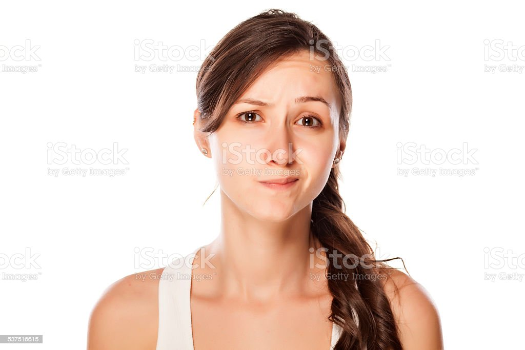 Dissatisfied young woman posing on a white background stock photo