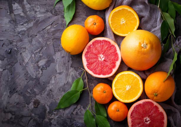 dissected fresh fruits. orange, grapefruit and tangerines - グレープフルーツ ストックフォトと画像