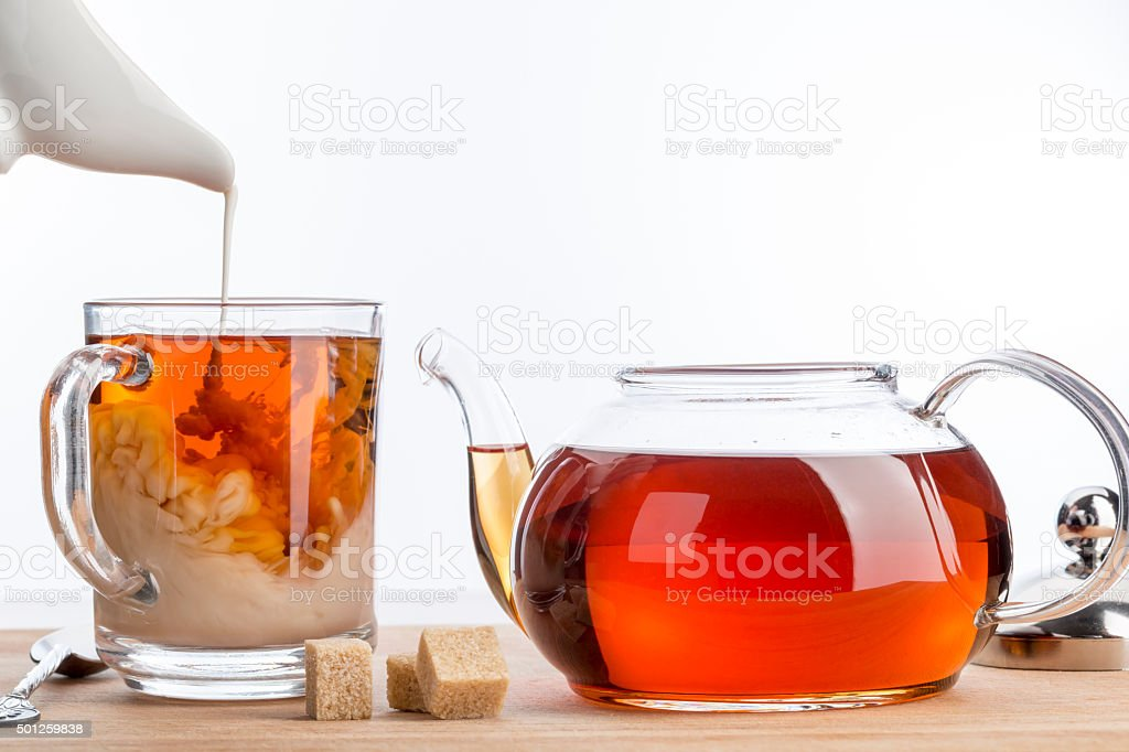 Dissolve milk in a cup of black tea. stock photo