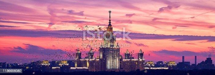 Dissolving texture of illuminated silhouette of famous Russian university on the dramatic background of sunset sky