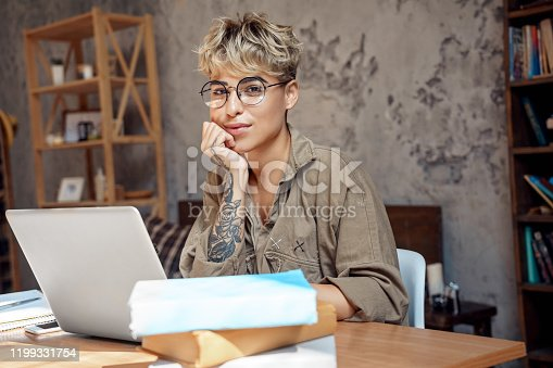 istock Distance Education. Young woman short hair in glasses sitting at desk studyinh on laptop looking camera smiling playful 1199331754