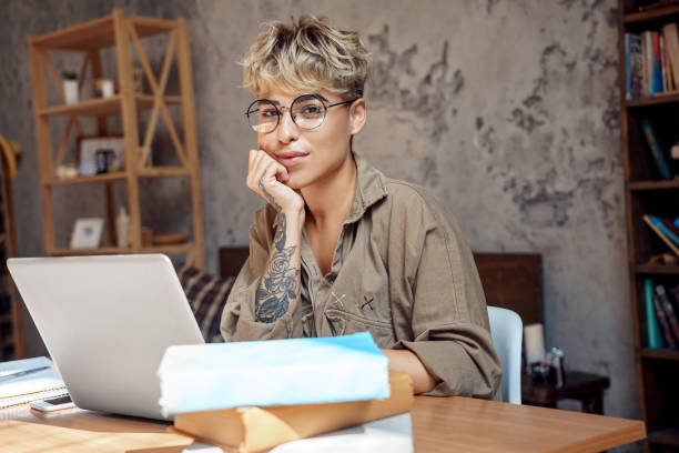 Distance Education. Young woman short hair in glasses sitting at desk studyinh on laptop looking camera smiling playful stock photo
