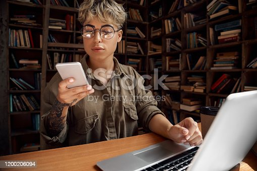 istock Distance Education. Young woman short hair in glasses sitting at desk studying on laptop browsing smartphone curious close-up 1200206094