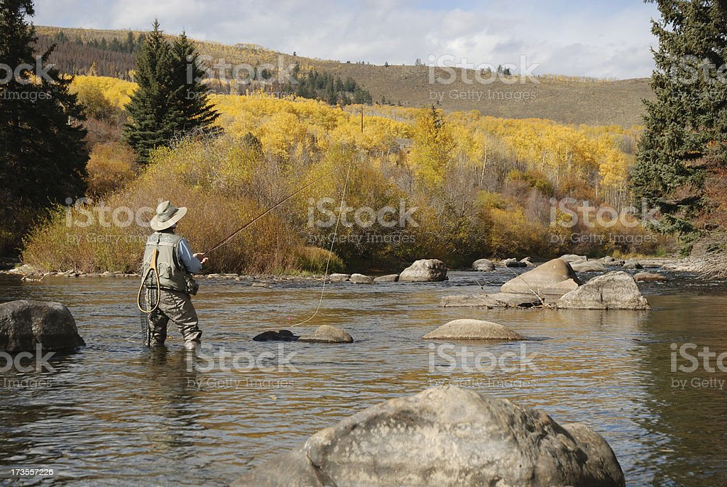 Distance image of a woman fly fishing in a river royalty-free stock photo