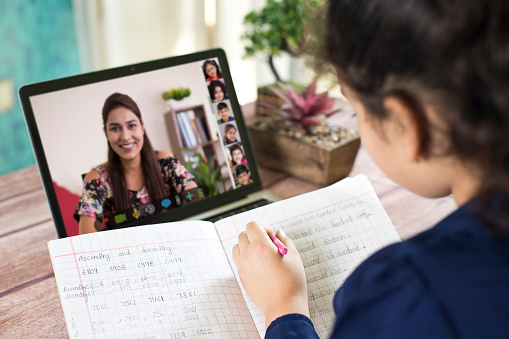 Girl participating in online education training class with teacher and other students using laptop at home