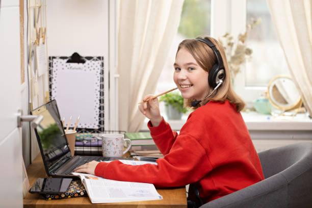 Distance Learning. Girls studying at home using laptop during coronavirus pandemic – zdjęcie
