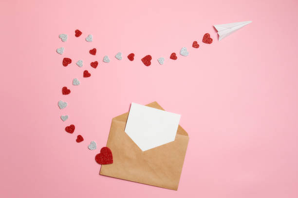 distance love concept, sending love letter, valentines day. kraft envelope with blank postcard and paper airplane flying on route made of heart shaped valentines cards lay on pink background desk - kartka na walentynki zdjęcia i obrazy z banku zdjęć