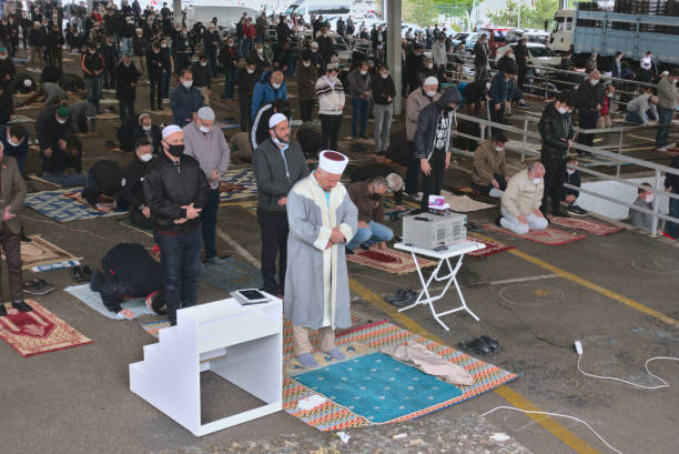 Distanced Muslim men praying in jumah prayer after 3 months quarantine in Turkey stock photo