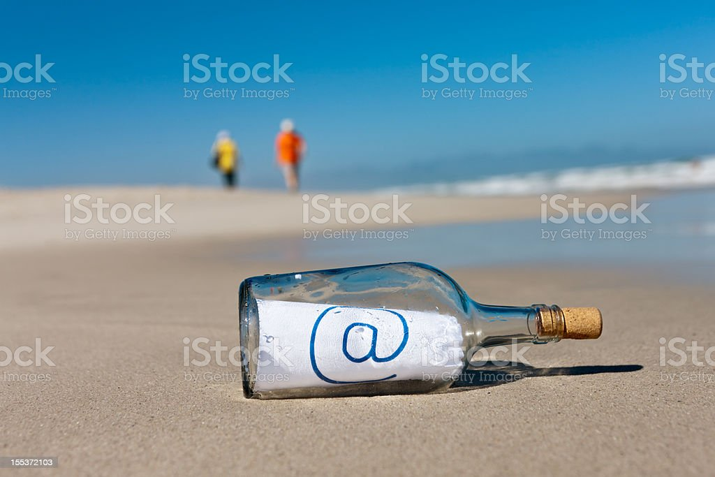 """Distant beachcombers ignore message in bottle saying """"@"""" royalty-free stock photo"""