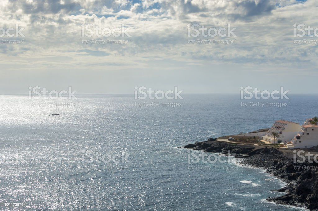 A distant boat sails in the late afternoon light on the Atlantic Ocean stock photo