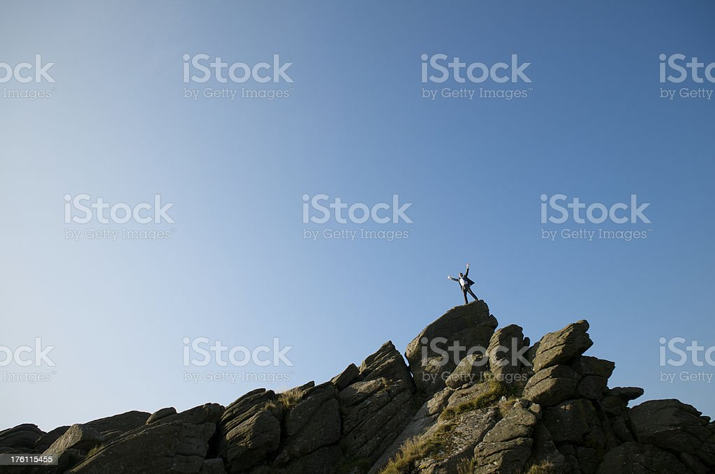 Distant Businessman Standing on Top of Rock Mountain Blue Sky royalty-free stock photo