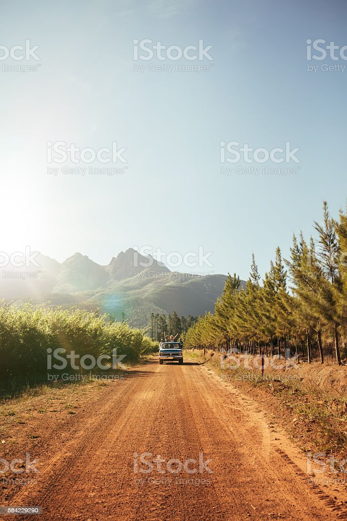 Distant car approaching on a rural dirt road stock photo