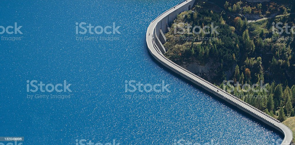 Distant dam with bright blue waters near a dense forest stock photo
