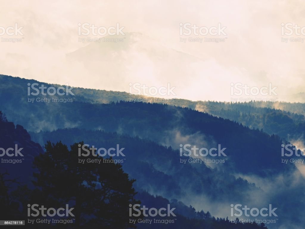 Distant mountain range and heavy clouds of colorful  mist above deep valleys royalty-free stock photo