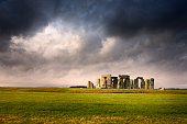 The sun pierces through a dense cloud layer to illuminate the iconic ancient temple of Stonehenge