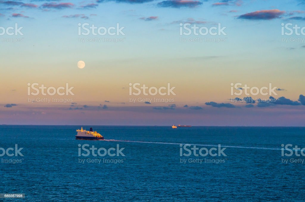 Distant ships crossing the English Channel at twilight stock photo