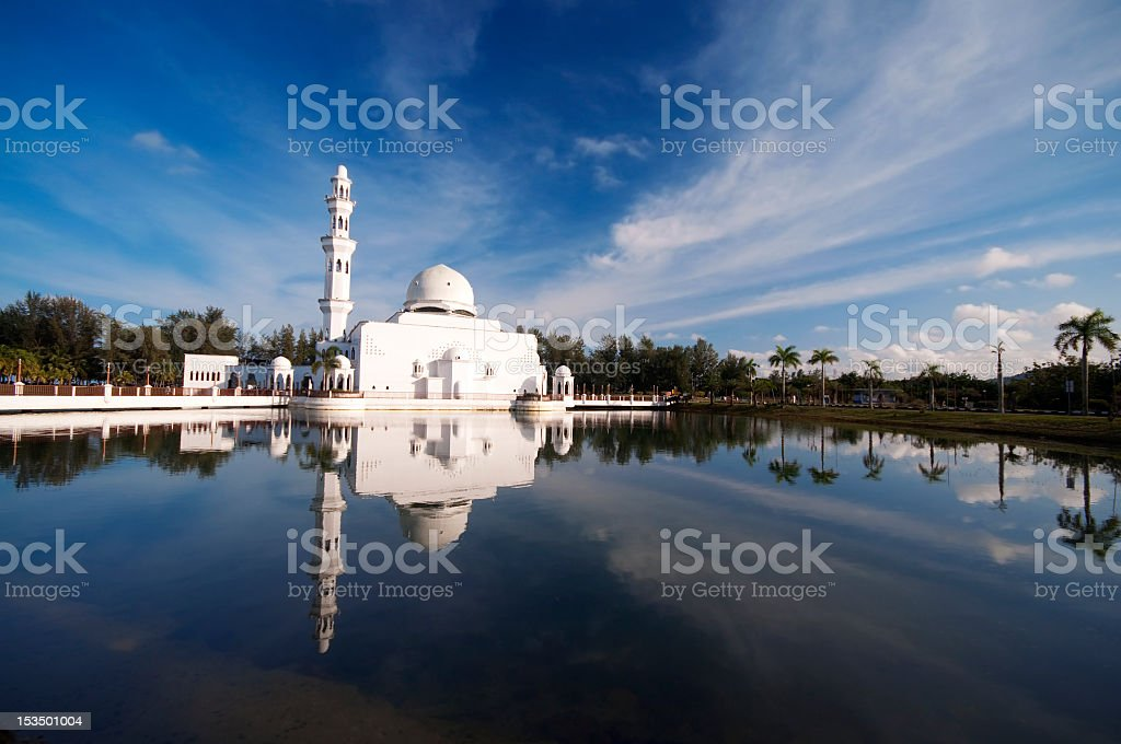 A distant shot of a mosque overlooking a lake stock photo