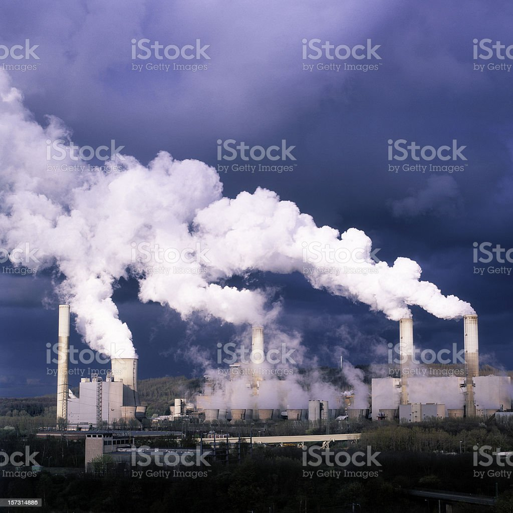 A distant view of smoke billowing from a power plant royalty-free stock photo