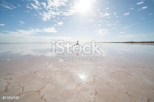 istock Distant woman jumping on salt lake 611312132
