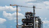 Distillation tower or column on blue sky with clouds background. Oil refinery plant. Refining complex.