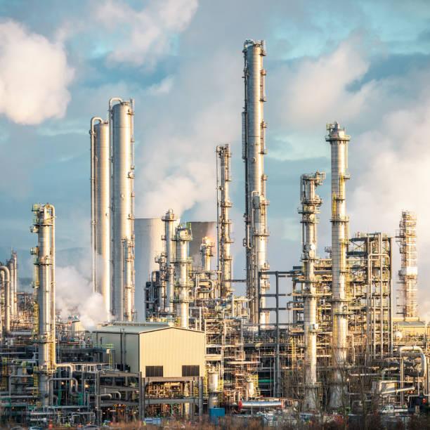 brenntürme an einer ölraffinerie - destillationsturm stock-fotos und bilder