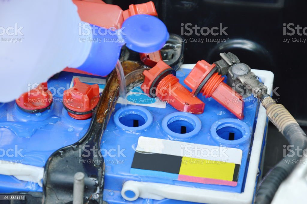 distilled water filling in car batteries for maintainence royalty-free stock photo