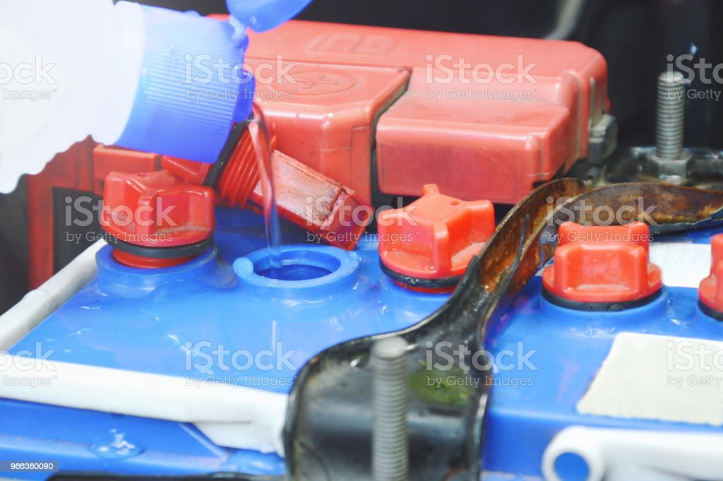 Distilled Water Filling In Car Batteries Stock Photo