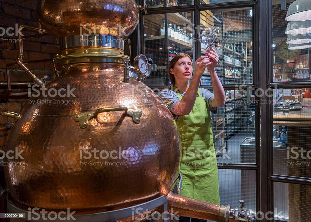 Distillery Boiler A female worker is sampling the alcohol produced from the copper distillery boiler. It is used to produce Gin and Whiskey. 2015 Stock Photo