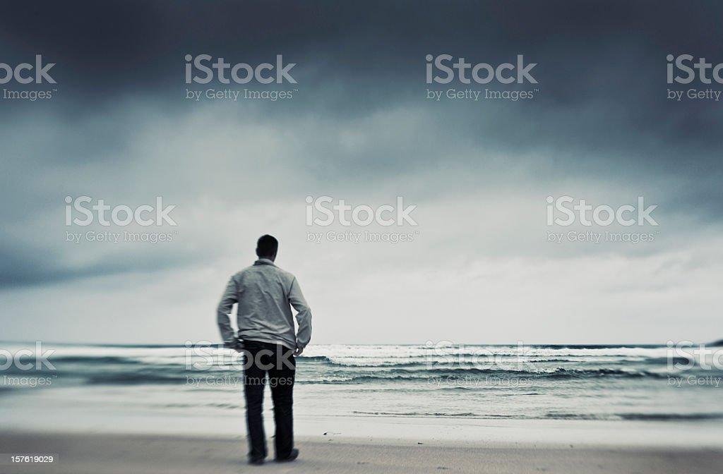 Distorted Lone man on rainy stormy beach royalty-free stock photo