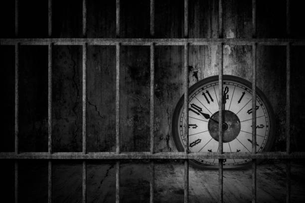 Verzerrte weiche Schmelzuhr ist in alten Gefängnissen verrosteten Metallstangen mit dunklem und dunklem Licht gefangen, Konzept des Verlustes von wertvolle Zeit und Falle im Geschäft – Foto