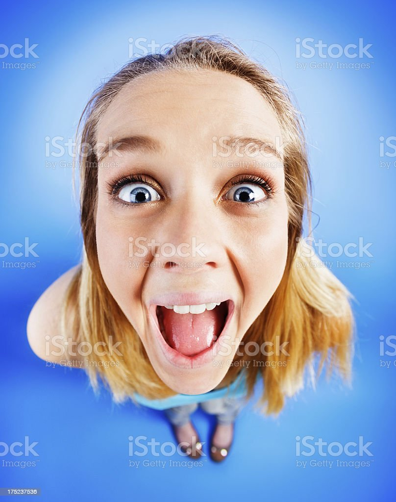 Distorted view of excited, wide-eyed blonde looking up open mouthed royalty-free stock photo