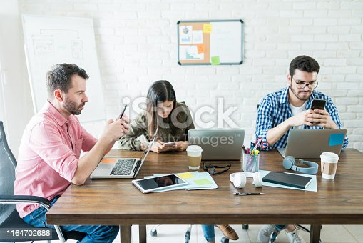 Business people sitting around conference table while socializing on mobile phones at office