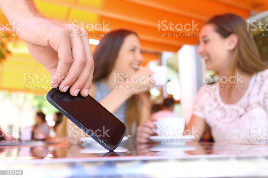 Amigos distraídos hablando en un bar y un ladrón robar teléfono - Foto de stock de Adulto libre de derechos