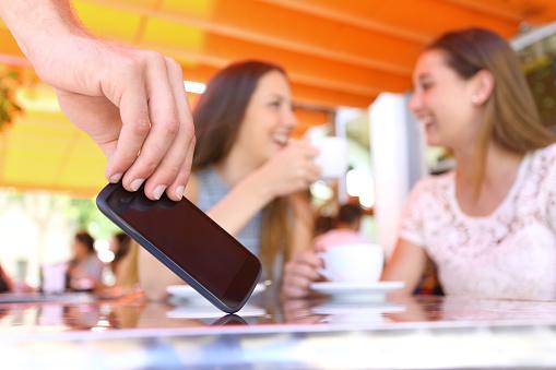 Amigos Distraídos Hablando En Un Bar Y Un Ladrón Robar Teléfono Foto de stock y más banco de imágenes de Adulto
