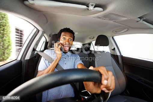 istock distracted man driving in car talking on smart phone 672846204